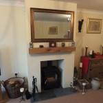 False chimney breast, riven slate hearth, oak beam and an Esse 500